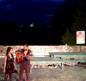 Sarai Davila and Archie Crisanto sing with fireworks in the background.