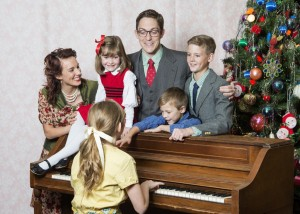 The Bailey family sings around the piano. They were an adorable onstage family. PC: Mark Philbrick